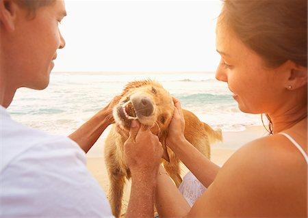 ビーチで犬と遊ぶカップル